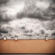 Stormy sky and tiled roof top Stock Photos
