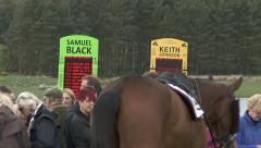 Spectators watch race horses in parade ring. Stock Footage