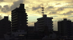Clouds Pass Over Silhouetted Apartment Building In Tokyo At Sunset Stock Footage