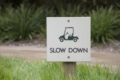 Slow down warning sign on field by dirt road Stock Photos
