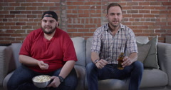 Watching Sports - One fan throws popcorn at another Stock Footage