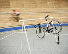 Bicycle hanging on rack at sports track - stock photo