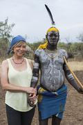 Unidentified European woman and man from Mursi tribe in Mirobey village - stock photo