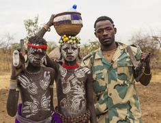 Boys from Mursi tribe and Ethiopian solder with machine guns in Mirobey village. - stock photo
