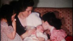 2181 - mom holds newborn son, his sisters close by - vintage film home movie Stock Footage