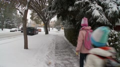 Two children walking to school in snow Stock Footage