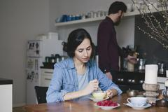 Young woman stirring coffee at kitchen table with man in background Stock Photos