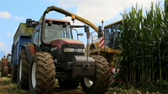 Thresher and tractor with trailer harvesting  corn Stock Footage