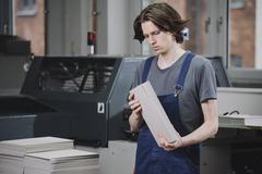 Young manual worker examining cardboard sheets in factory Stock Photos
