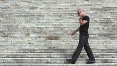 nervous man walking on the steps and talking with the mobile phone - stock footage