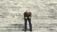 young man exults on the steps: walking man rejoices for his success - stock footage