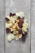 Directly above shot of potato and beetroot chips on wooden table Stock Photos