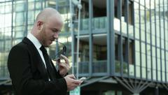 Houghtful businessman texting a message with the smartphone Stock Footage