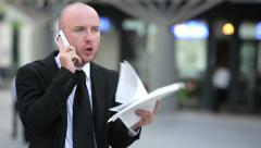 Angry businessman arguing with documents in his hands during a phone call Stock Footage