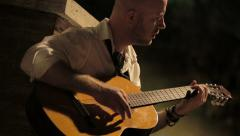 Lonely man playing the guitar in the night Stock Footage