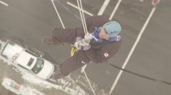 Two men rappel off Calgary Tower from above, zoom out Stock Footage