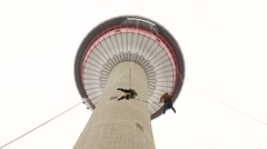 Two men rappel off Calgary Tower, zoom in Stock Footage