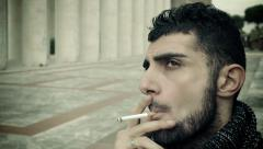 Thoughtful man smoking outdoor in the sun Arkistovideo