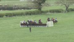 Racehorses jump a fence during a race. Stock Footage