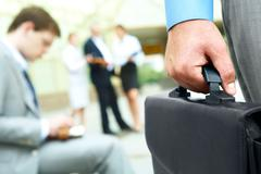 Hand with briefcase - stock photo