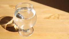 Glass of water slow slide Stock Footage
