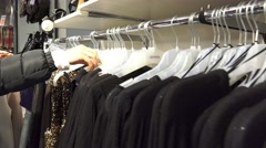 4k Woman's hands run across a rack of clothes, browsing in a boutique. UHD st Stock Footage