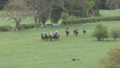 Racehorses jump three fences during a race - long clip. Stock Footage