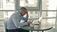 Businessman comparing bad results on cellphone and laptop Stock Footage