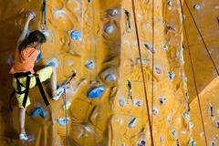 Climbing teenager girl to the top of wall - stock photo