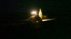 Bulldozer working in the dark around the clock, long shot - stock footage