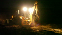 Bulldozer working at night, long shot Stock Footage