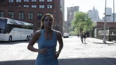 Pretty jogger blue tank top training NYC Brooklyn Bridge landmark exercising 4K Stock Footage