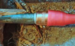 Hot water pipe on broken floor - stock photo