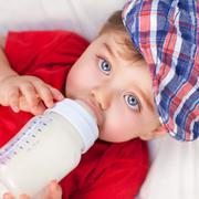 Stock Photo of Hungry little boy drinking milk