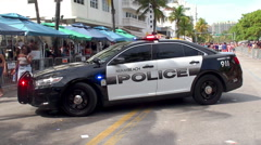 Miami Police car with emergency lights activated at the Ocean drive Stock Footage