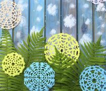 Carved green fern leaves and paper snowflakes on a blue wooden background - stock photo
