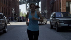 Female jogger running in slow motion, 4K, Brooklyn Bridge in background, NYC Stock Footage