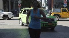 Girl jogging street green taxicab behind Brooklyn Bridge slow motion 4K NYC Stock Footage