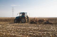 Farmer in tractor preparing land Kuvituskuvat