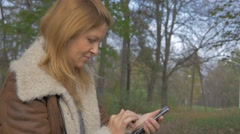 Woman using mobile phone  outdoors 1080p HD video - Casual weared blond woman Stock Footage