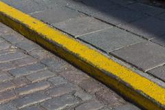 Yellow curb stone border - stock photo