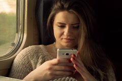 Woman using smartphone while traveling by train, steadycam shot - stock footage