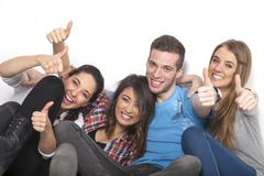 Four friends show thumbs up sign - stock photo