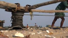Fishermen pull in their boats with a manual device on a beach in India Stock Footage