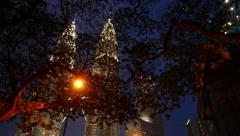 Petronas Twin Towers through tree leafage in dusk, night time Stock Footage