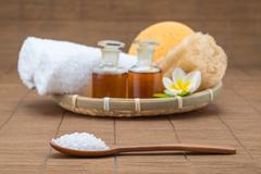 spa bath, salt spoon, towel sponge essential oil and flower for spa health - stock photo