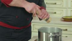 Professional chef adding salt, pepper and spices to meal Stock Footage