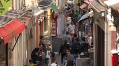 Tourists walk down typical narrow street in old town Antibes, France Stock Footage
