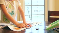 A little girl coloring in her coloring book Stock Footage