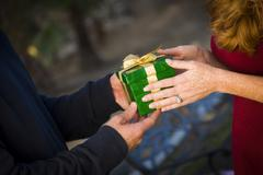 Hands of Man and Woman Exchanging a Wrapped Christmas Gift. - stock photo